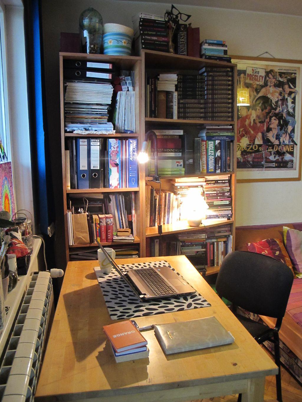 Loc de birou la masa din sufragerie. Una dintre etajere are o forma atipica care permite adapostirea volumelor cu coperte atipice, dar se vede si bine din camera fiind mai ingusta la unul dintre capete.
