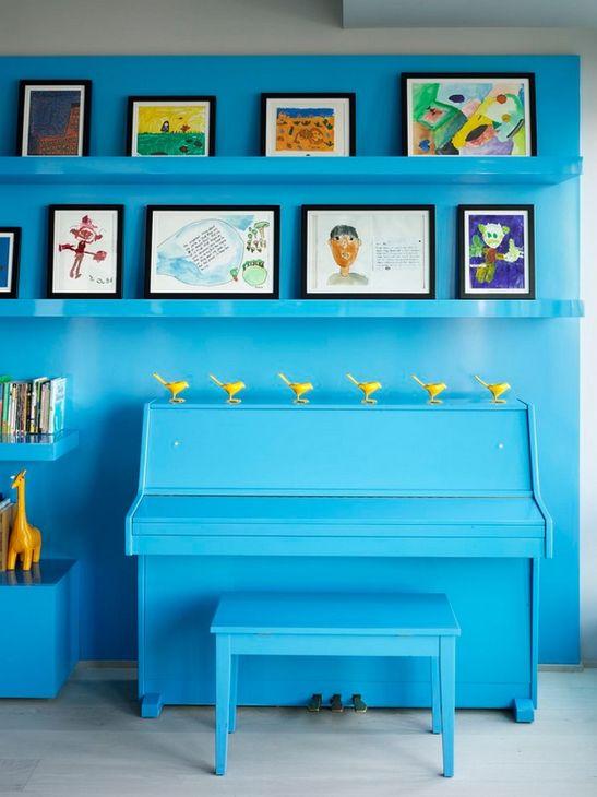 Detaliu din living cu pianina si desenele copiilor