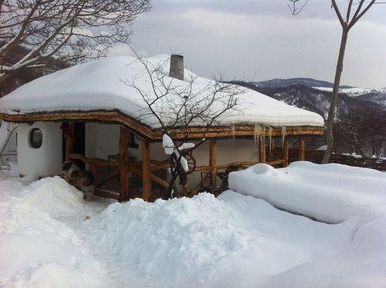 Casa mica cu acoperis de pamant iarna